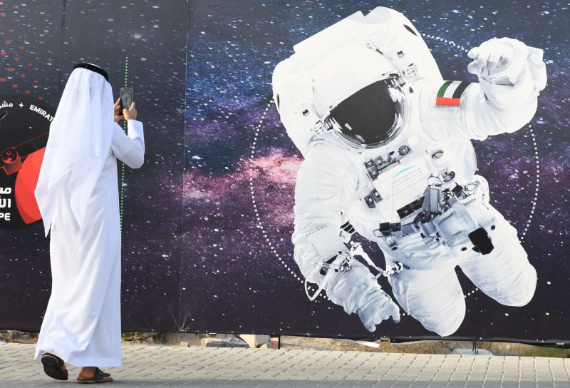 A man takes a picture of an illustration depicting an astronaut with the Emirati national flag outside Mohammed Bin Rashid Space Centre (MBRSC) in Dubai on September 25. (AFP)