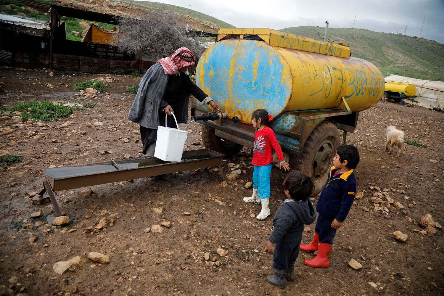 A Palestinian man fills a container with water from a tank in the Bedouin village of Al-Maleh in Jordan valley in the Israeli-occupied West Bank