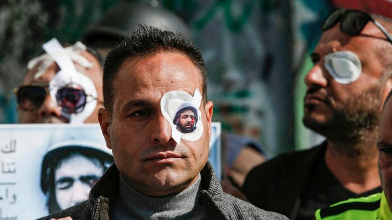 A Palestinian journalist wears a paper eye patch during a demonstration in Bethlehem in the occupied West Bank on November 17, 2019, in solidarity with Muath Amarneh. (AFP)