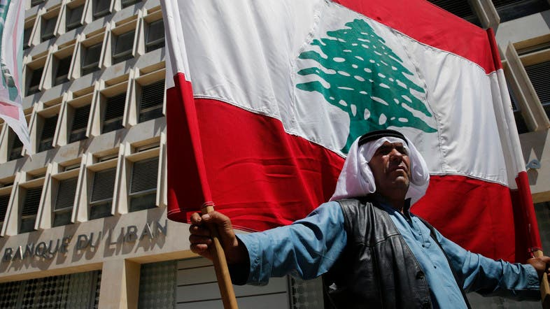 A retired Lebanese soldier holds a national flag during a protest in front of the central bank headquarters in Beirut. (File photo: AP)