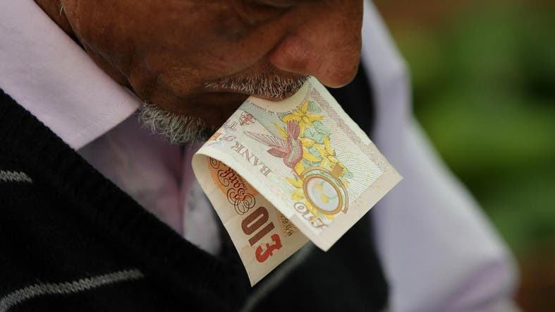 A trader holds a ten pound sterling note in his mouth as he prepares a customer's order at Whitechapel Market in east London. (File photo: AFP)
