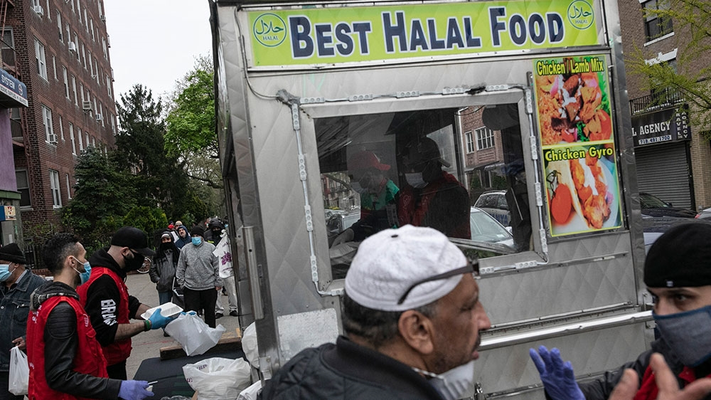People queue up for free food handed out by volunteers from Muslims Giving Back, in red vests, in the Bay Ridge neighbourhood of Brooklyn [Wong Maye-E/AP Photo]