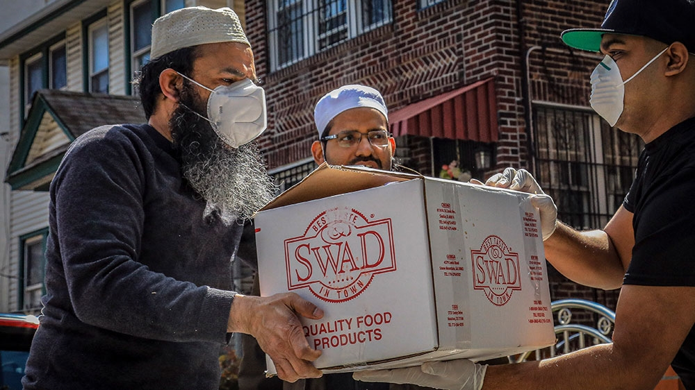 Imam Mufti Mohammed Ismail, centre, and volunteer Mohammad Q Ullah, left, delivers a box of food supplies prepared at An-Noor Cultural Center and masjid for those impacted by COVID-19 restrictions
