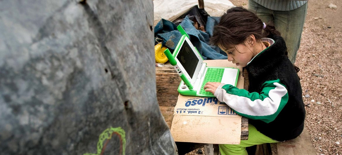 Young girl in Uruguay uses her laptop to study at home.