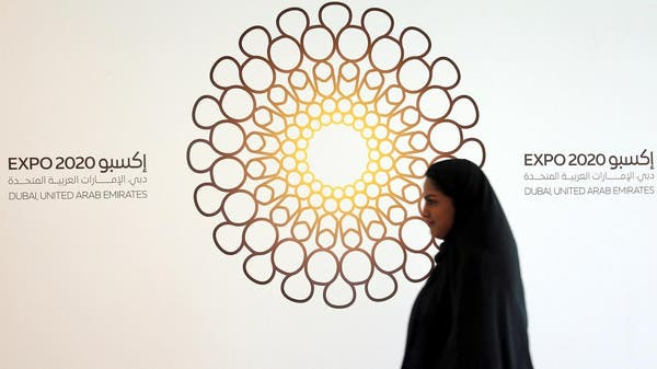 A woman walks past the logo of the Expo 2020 in Dubai, United Arab Emirates, April 3, 2017.