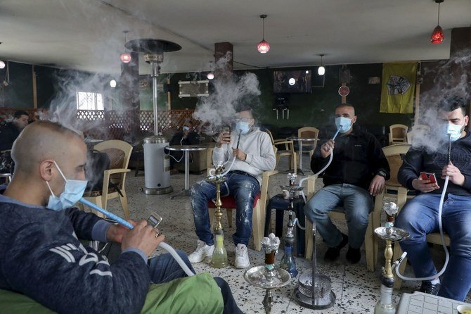Palestinian men smoke the shisha (waterpipe) while wearing protective masks at a coffee shop in the West Bank city of Hebron, on March 7, 2020, amid fears of the spread of the novel coronavirus. (File/AFP)