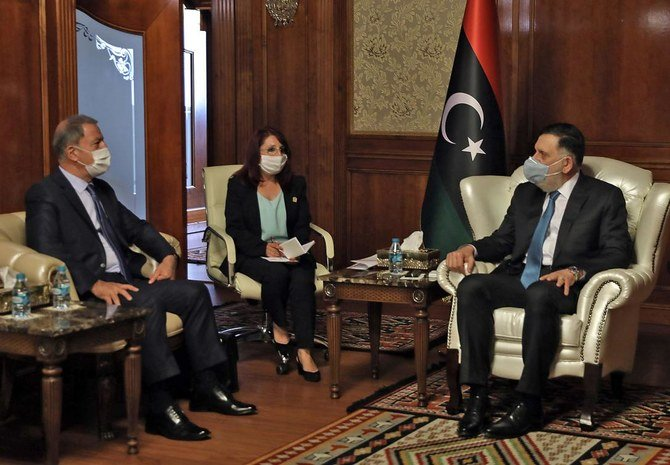 Fayez Al-Sarraj (R), Prime Minister of Libya's Government of National Accord (GNA) receives Turkish Defense Minister Hulusi Akar (L), in the Libyan capital Tripoli on July 3, 2020. (AFP)