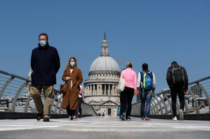People wearing face masks cross Millennium Bridge, as the spread of the coronavirus disease (COVID-19) continues, in London, Britain, April 25, 2020. (Reuters)
