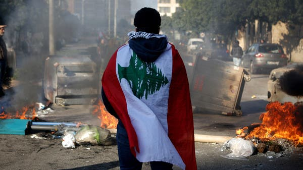 In this file photo taken on January 14, 2020, a Lebanese anti-government protester, wrapped in a national flag, stands in front of a road blocked with burning tyres and overtunrned garbage dumpsteres in Beirut. (File photo)