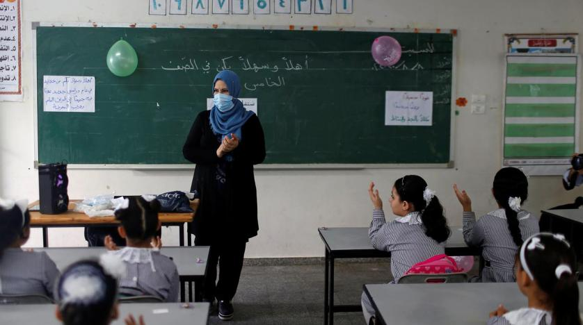 A teacher gestures as Palestinian students sit in a classroom at a UN-run school