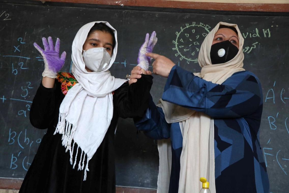 A teacher demonstrates to children how to protect themselves against the coronavirus at a school in Herat, Afghanistan, as centres of learning reopened.