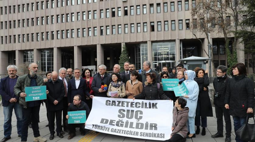 Journalists outside an Ankara court protest over the jailing of colleagues with a banner reading in Turkish 'journalism is not crime', March 10, 2020